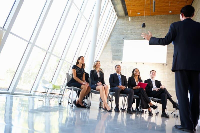 Delegater som lyssnar till högtalaren royaltyfri fotografi