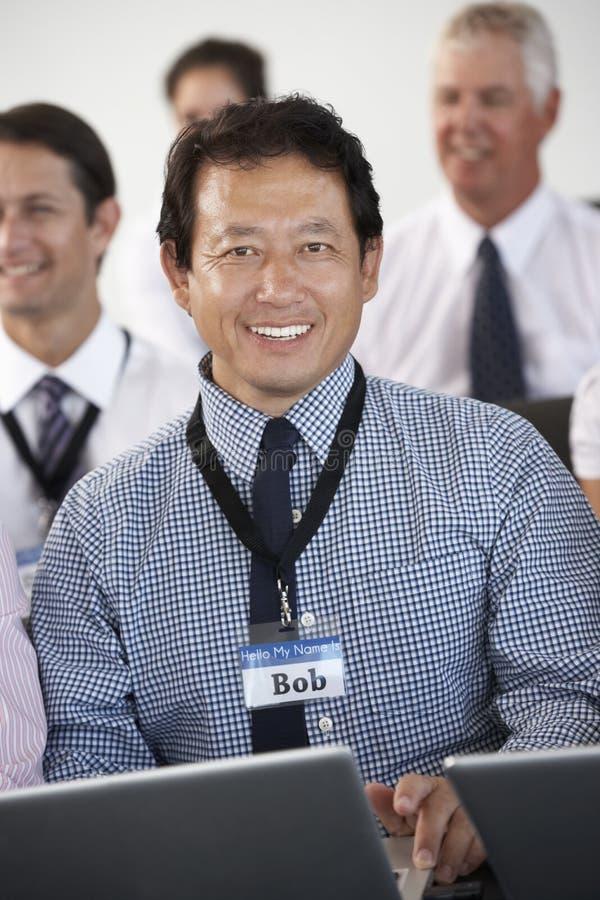 Delegato maschio che ascolta la presentazione alla conferenza che fa le note sul computer portatile fotografia stock