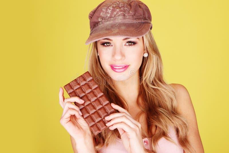 Deleite bonito do chocolate da terra arrendada da mulher foto de stock