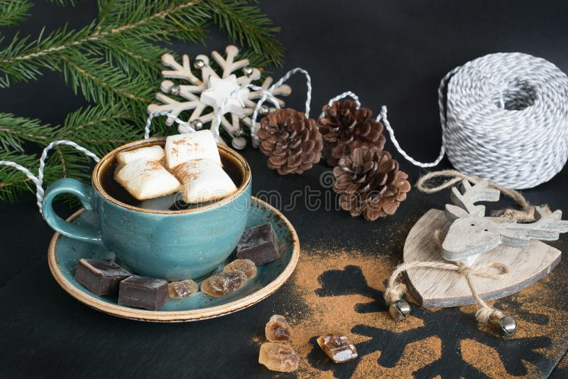 Deleites do Natal Xícara de café com marshmallow e decoração do feriado em um fundo preto com ramos de árvore do Natal imagem de stock royalty free