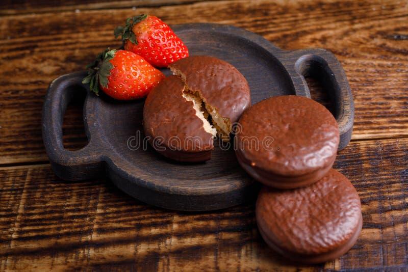 Deleites românticos das morangos e das cookies do chocolate em uma placa de madeira Um deleite para amado Dia do `s do Valentim imagens de stock royalty free