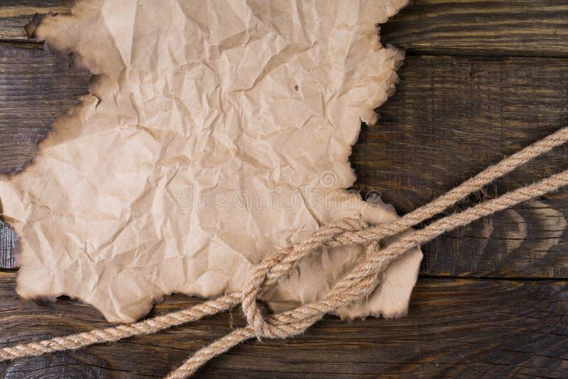 Delen av det gamla brända pergamentet och en fnuren av hamparepet som ligger på tabellen med en kork, avslutar sig Ram för din et arkivfoton
