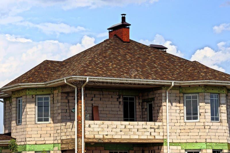 Delen av ett privat hus av vit tegelsten med en brunt belade med tegel taket mot himlen royaltyfri foto