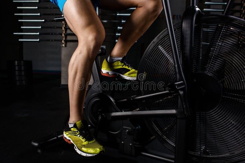 Delen för närbilden för sidosikten av den unga mannen i sportar skor att cykla på idrottshallen royaltyfri bild