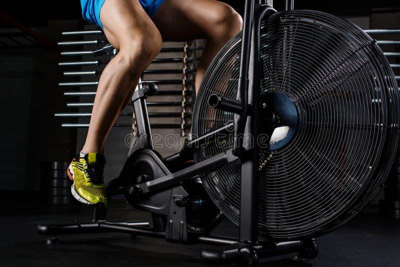 Delen för närbilden för sidosikten av den unga mannen i sportar skor att cykla på idrottshallen arkivbilder