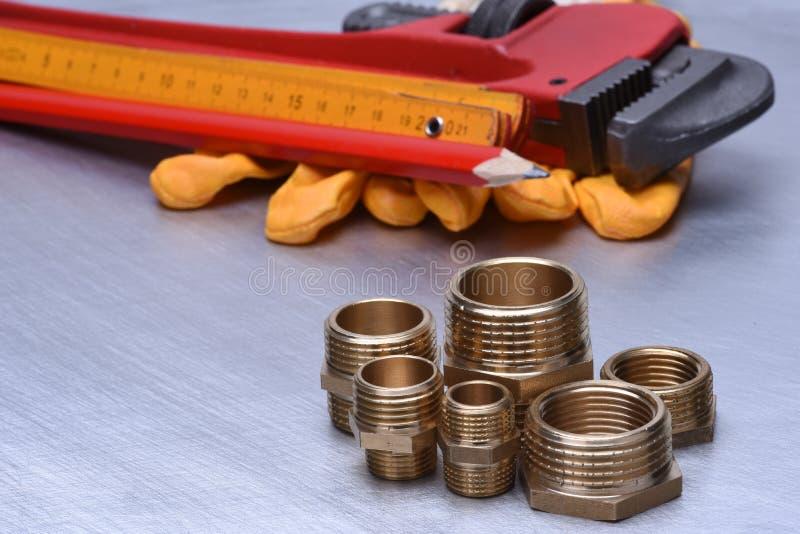 Delen van loodgieterswerkmontage met moersleutel en hulpmiddelen royalty-vrije stock afbeelding