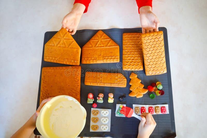 Delen van peperkoekhuis op het bakken en het verfraaien worden voorbereid die Kerstmis traditionele activiteit en zoete cake Acti royalty-vrije stock afbeelding
