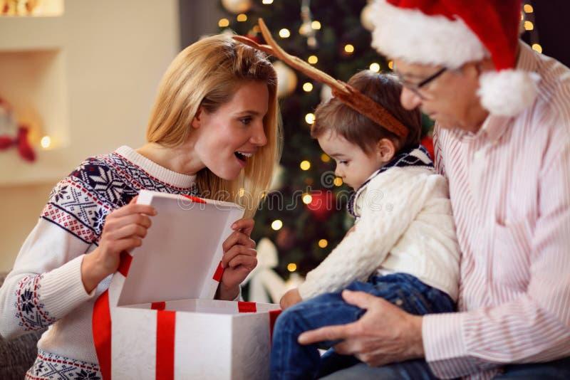 Delend gift bij Kerstmis het glimlachen moeder aanwezige geven aan zoon stock fotografie
