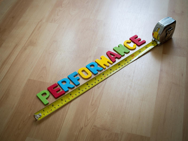 Deletreo de la palabra y x22; Performance& x22; y cinta métrica amarilla en fondo de madera del piso Concep de la medida de funci fotografía de archivo libre de regalías