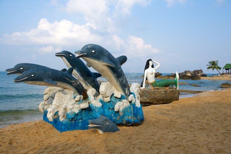 Delfin- och sjöjungfruskulptur på stranden royaltyfri bild