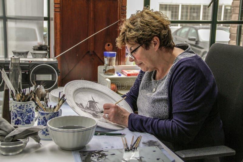 Delft, holandie Marzec 2018 porcelan malarzów - Królewska Delft fabryka - zdjęcia stock