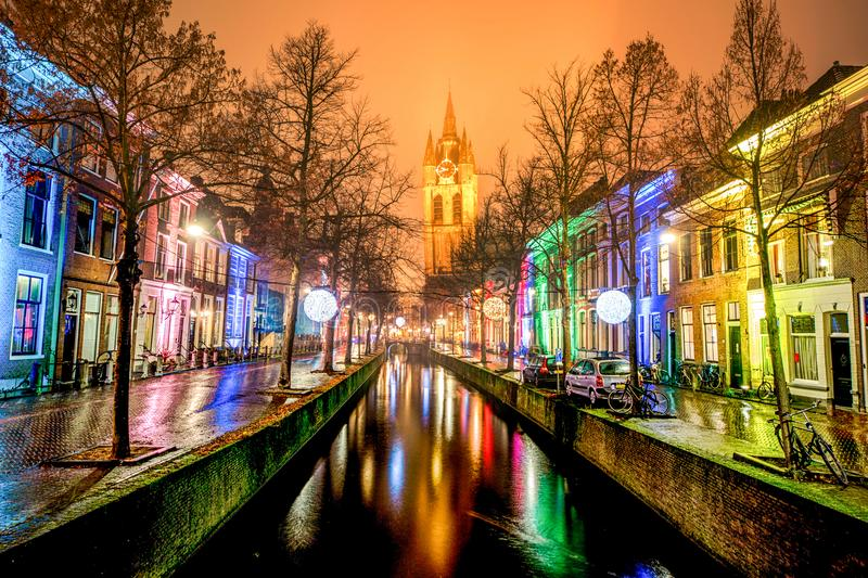 Delft light festival season. View of the Delft canal bordered with enlighten color houses and the tower of the old church reflecting on the canal, Netherlands stock photos