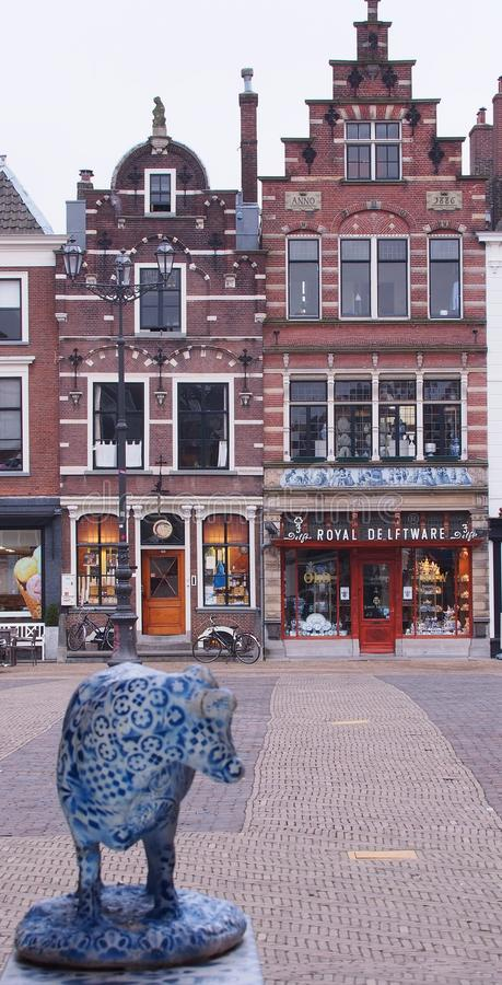 Delft pottery cow looking towards a Royal Delftware pottery outlet stock image
