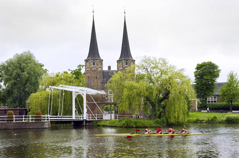 Delft Rowing. A rowing team in a coxed four rowing past a historic, fortified, city gate in Delft, the Netherlands stock image