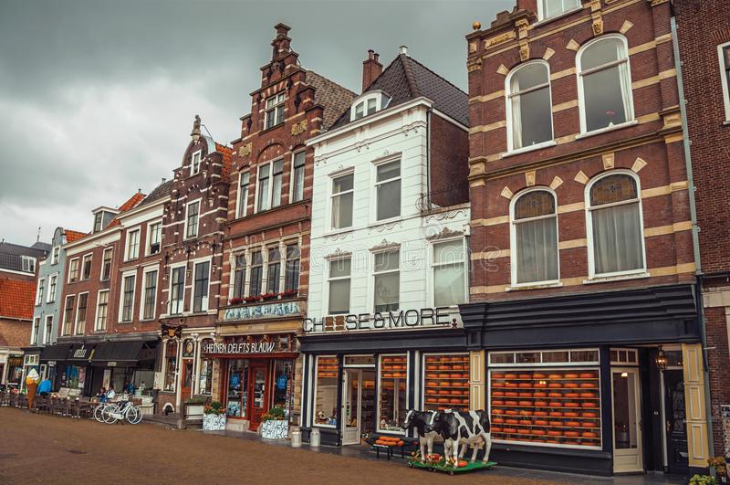 Market Square and old brick building facade with cheese shop on cloudy day in Delft. stock images