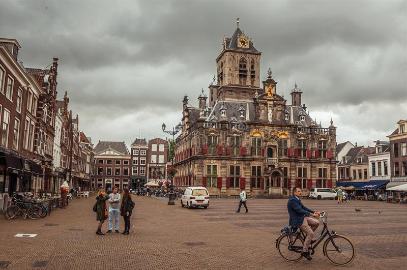 People on Market Square and decorated Gothic City Hall building on cloudy day in Delft. stock image