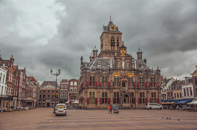 People on Market Square and decorated Gothic City Hall building on cloudy day in Delft. royalty free stock photos