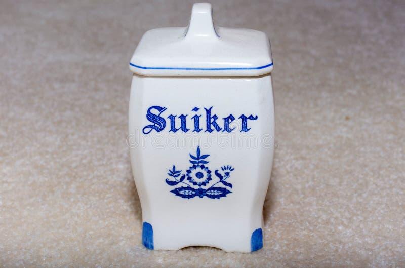DelftfajansblåttSugar Suiker behållare Berömda porslinsouvenir från Holland/Nederländerna på texturerad beige bakgrund fotografering för bildbyråer