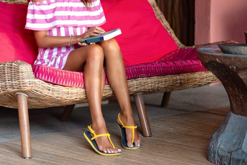 Delgado se alza de la mujer hermosa que se sienta en un sof? rosado y que guarda un libro Interior en estilo ?tnico Cierre para a fotos de archivo