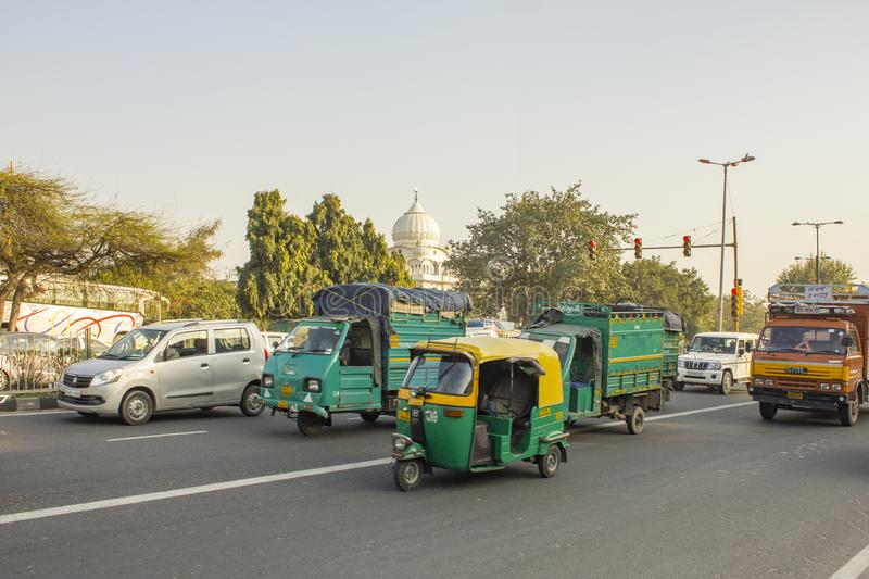 Indian green moto trucks and rickshaws in city traffic on a background of green trees and the dome of a stock photo