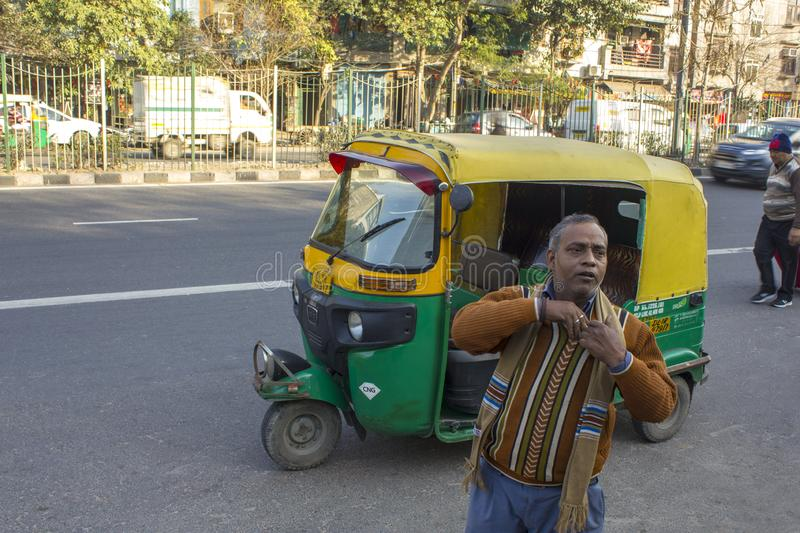 Indian rickshaw driver takes the money against the backdrop of a green-yellow taxi and city traffic stock images