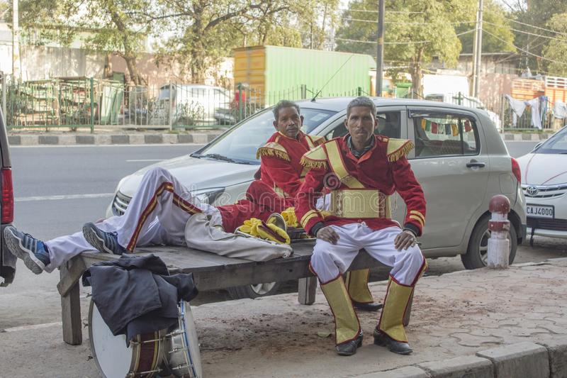 Indian street performers musicians with drums in red dress uniform are resting on the bench royalty free stock photo