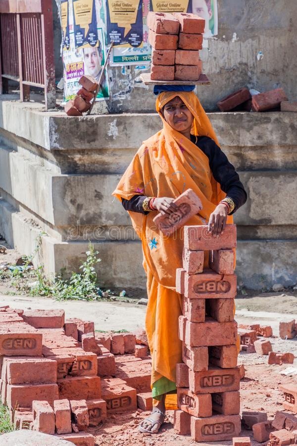 DELHI, INDIA - OCTOBER 22, 2016: Female worker carrying a load of bricks on her head in the center of Delhi, Indi stock photography