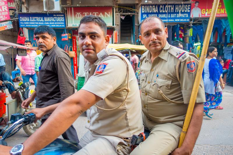 DELHI, INDIA - SEPTEMBER 25 2017: Close up of unidentified police officers over a motorcycle looking at camera in the. Center of the city in Paharganj, Delhi stock photos