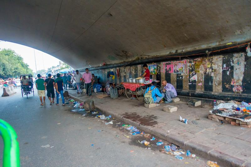 DELHI, INDIA - SEPTEMBER 25, 2017: Unidentified people living in the streets of the city under a bridge juveniles. Catching sleep on footpath, delhi, india royalty free stock images