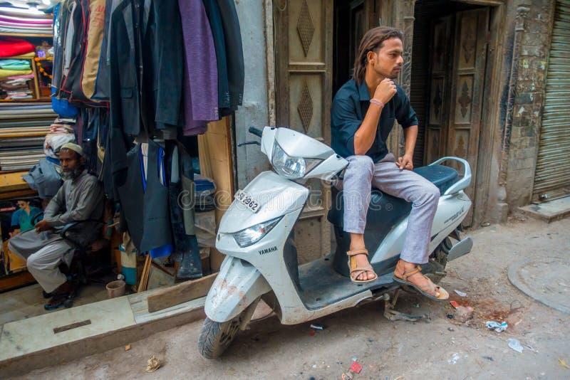 DELHI, INDIEN - 25. SEPTEMBER 2017: Nicht identifizierter Mann, der über seinem Motorrad wartet in die Straßen in Paharganj sitzt stockfotos