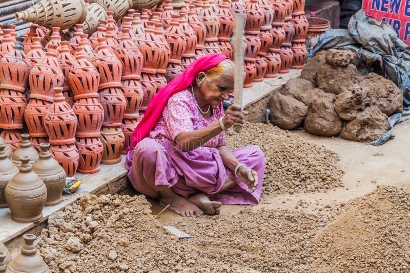 DELHI, LA INDIA - 22 DE OCTUBRE DE 2016: Mujer mayor que machaca pedazos de arcilla en el centro de Delhi, Indi imágenes de archivo libres de regalías