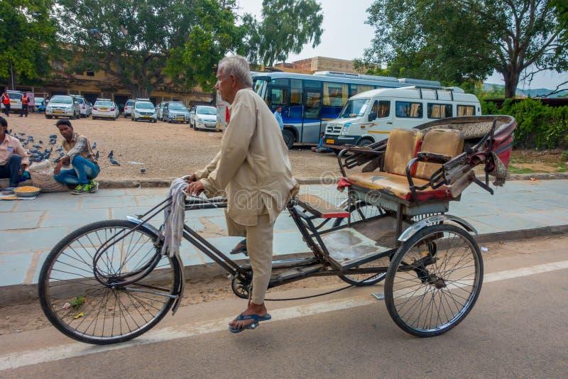 DELHI, LA INDIA - 19 DE SEPTIEMBRE DE 2017: El hombre no identificado biking en la calle, allí es mucho estancia turística en est foto de archivo