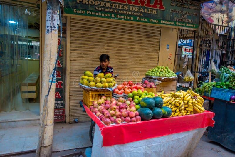 Delhi, la India - 25 de septiembre de 2017: Hombre no identificado en el aire libre de la pequeña tienda al por menor con las fru fotos de archivo