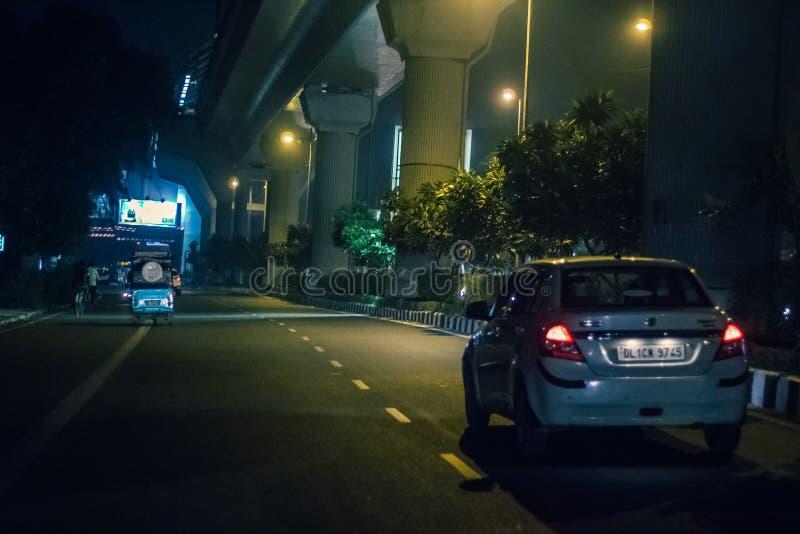 Deli, Índia - 19 de março de 2019: Ideia da rua da vida de povos e de veículo da Índia nas ruas na noite imagens de stock
