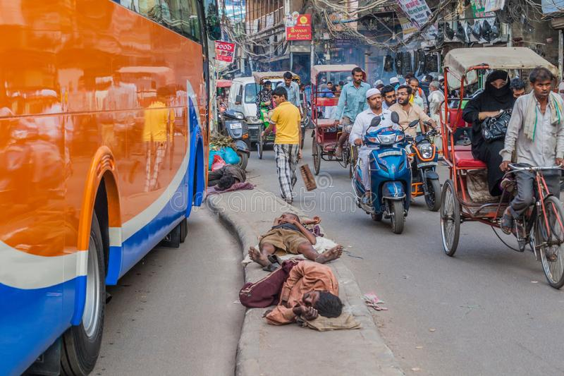 DELI, ÍNDIA - 22 DE OUTUBRO DE 2016: Tráfego e os sem-abrigo em uma rua no centro de Deli, Indi fotos de stock royalty free
