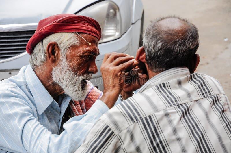 Deli, Índia, o 3 de setembro de 2010: Orelha indiana o do ` s do homem da limpeza do homem foto de stock