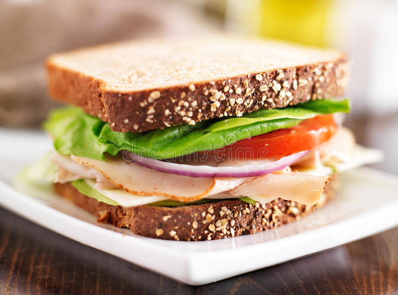 Deli meat sandwich with turkey, tomato, onion, and lettuce. Shot with selective focus royalty free stock images