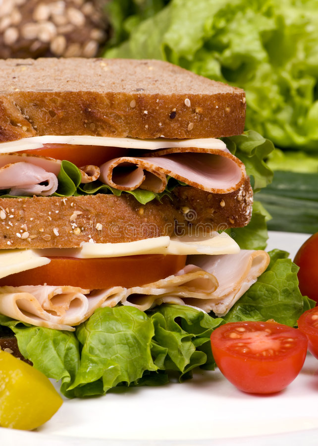 Deli Sandwich 009. A fresh deli sandwich with tomatoes swiss chees, lettuce and lots of meat royalty free stock photography