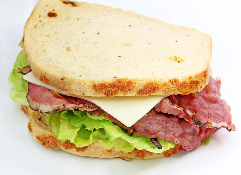 Deli Sandwich. Thin slices of pastrami deli meat, a slice of cheese and sandwich veggies in a white specialty bread royalty free stock image