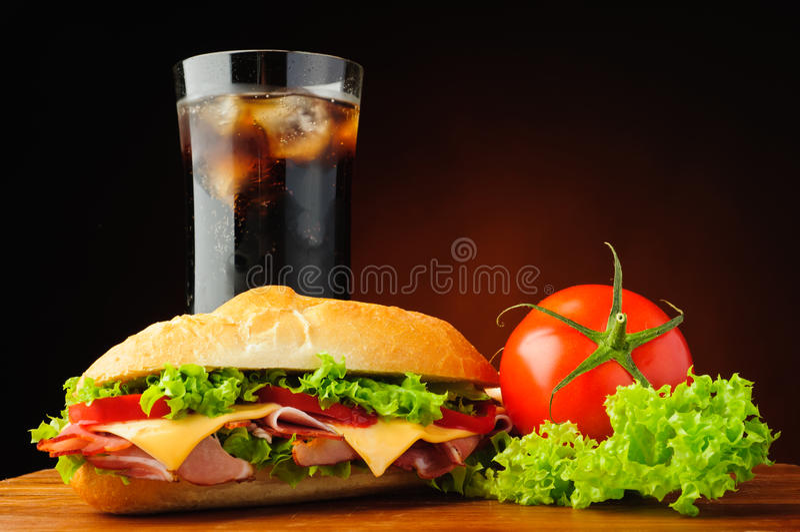 Deli sub sandwich. Still life with deli sub sandwich, fresh vegetables and cola soft drink stock photo
