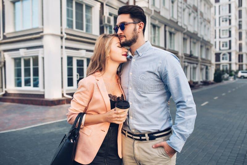 Delicadamente o par está abraçando na rua na cidade O indivíduo considerável é camisa azul e os óculos de sol olham seriamente, c imagem de stock royalty free
