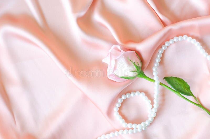 Delicadamente o rosa aumentou com uma colar da pérola na tela do cetim imagens de stock