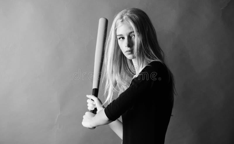 Delicado mas aptly Retroceda fora Centrado sobre o resultado A mulher aprecia o jogo de basebol do jogo Bast?o de beisebol louro  fotografia de stock