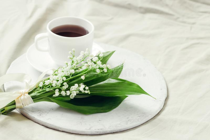 Bouquet of fresh lilies of the valley decorated with silk ribbon and freshly brewed coffee on a wooden tray on the bed. Delicate bouquet of fresh lilies of the royalty free stock photography
