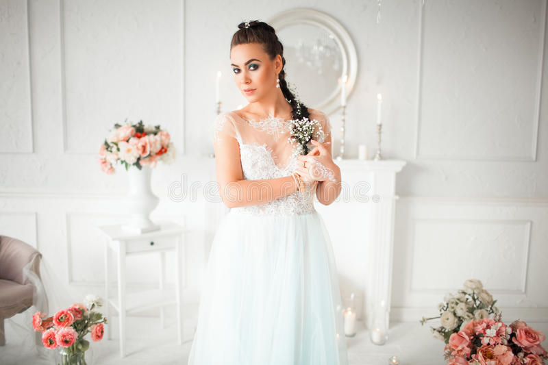 Delicate bride with flower in her hair stands in the room. The girl`s body painted with mehendi. Amid the candles. Delicate bride with flower in her hair stands royalty free stock image