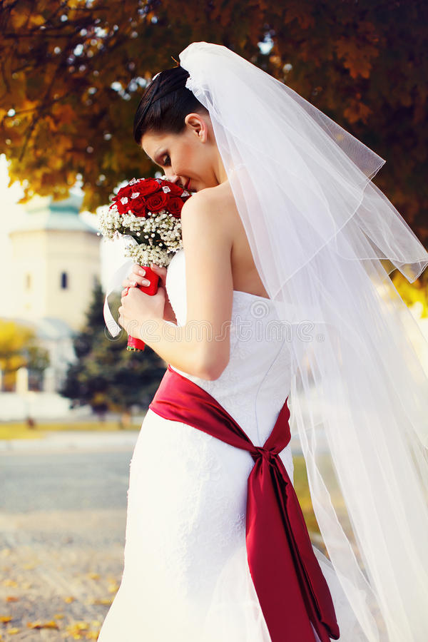 Delicate bride with a red belt on her dresss smells a wedding bo. Uquet a royalty free stock photography