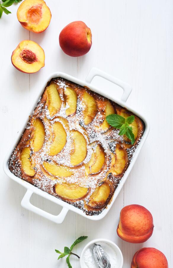 Delicate cake with peaches sprinkled with powdered sugar on a black concrete background royalty free stock photography