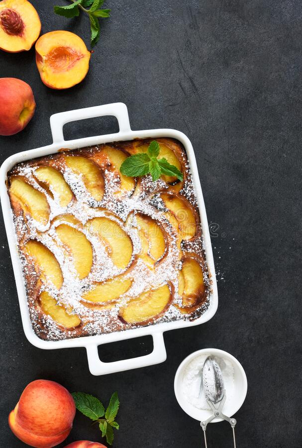Delicate cake with peaches sprinkled with powdered sugar on a black concrete background stock photos