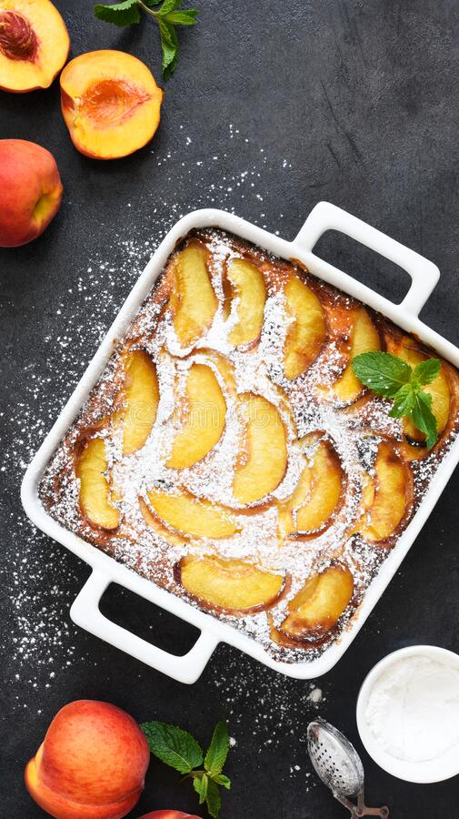 Delicate cake with peaches sprinkled with powdered sugar on a black concrete background stock photo