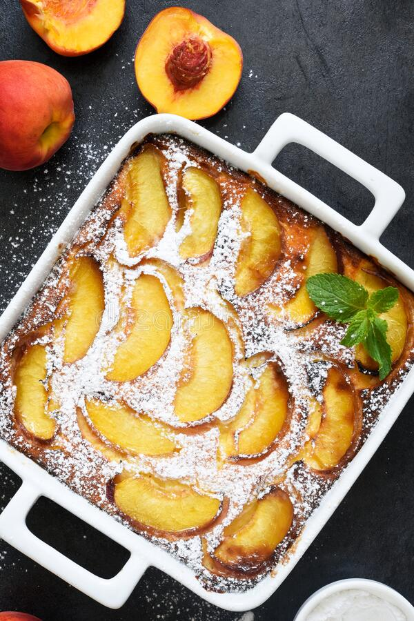 Delicate cake with peaches sprinkled with powdered sugar on a black concrete background stock photography